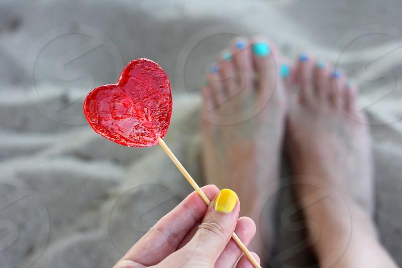 Holding a heart shaped lollipop at the beach bare feet nail polish sweet summer photo