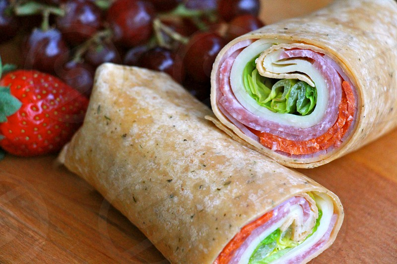 brown vegetable dish roll beside red strawberry and purple grapes on brown wooden table photo
