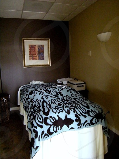 Spa suite massage table and accessories brown and tan room with teal and brown spread photo