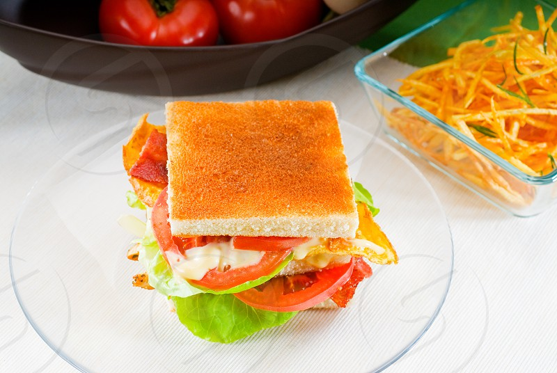 fresh and delicious classic club sandwich over a transparent glass dish photo