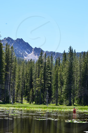 Boy fly fishing in remote location lake trees mountains blue sky photo