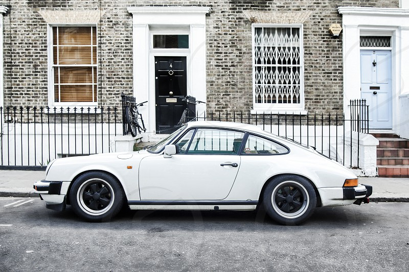 white two door porsche parked before grey stone building with black wrought iron fence photo