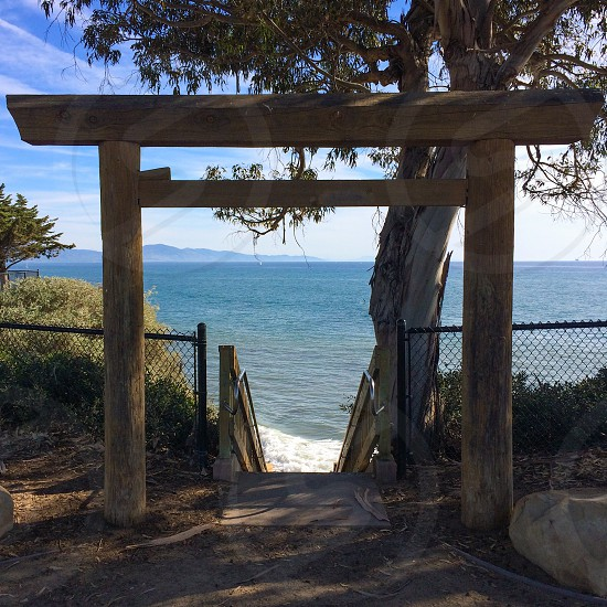 wood torii gate leading to outdoor staircase leading to large body of water photo