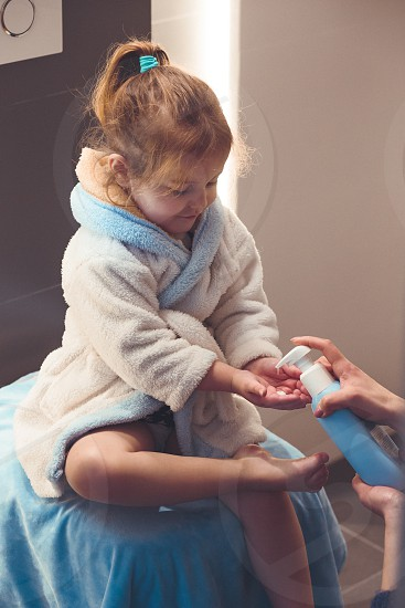 Mother applying moisturizing cream on her daughter's legs after bath. Mom caring about her child. Girl sitting in bathroom wearing bathrobe photo