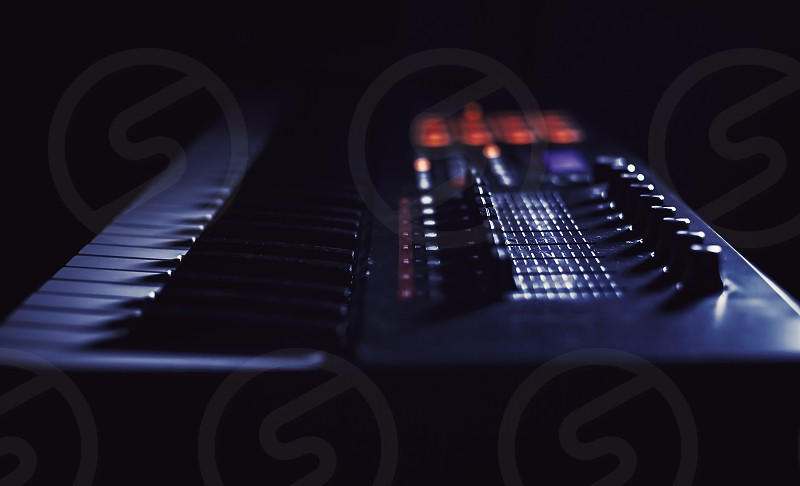 Closeup view of modern midi keyboard dark background and strong highlights.  photo