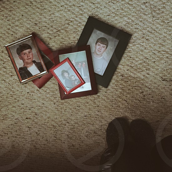 portrait photographs in frames on gray carpet flooring photo