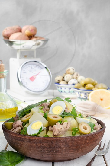 Potato salad on brown plate with ingredients on light background photo