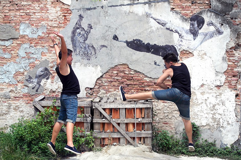 2 man in black tank top near gray and brown wall photo