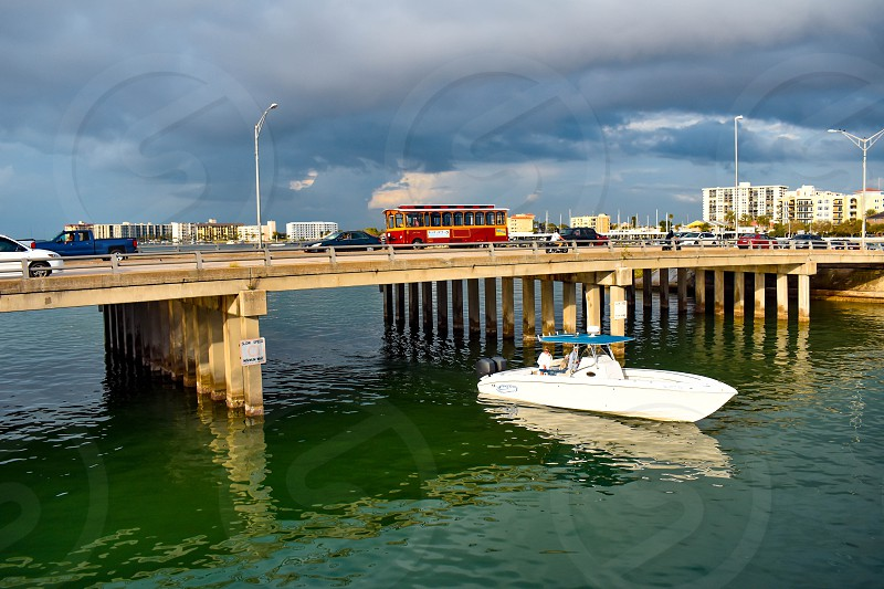 Clearwater Beach Florida. January 25 2019 Colorful Jolley Trolley and bowrider boat crossing the bridge in Gulf Coast Beaches. photo