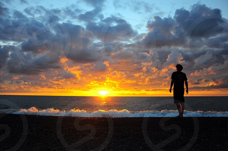 person standing on beach under sunset photo