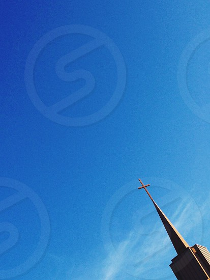 cross on building spire tower under clear blue sky photo