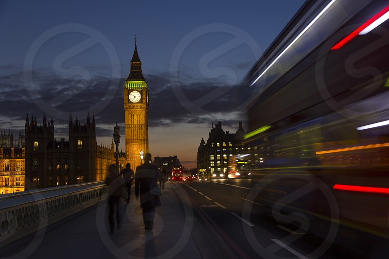 Big Ben at night and London Bus passing by at night. photo