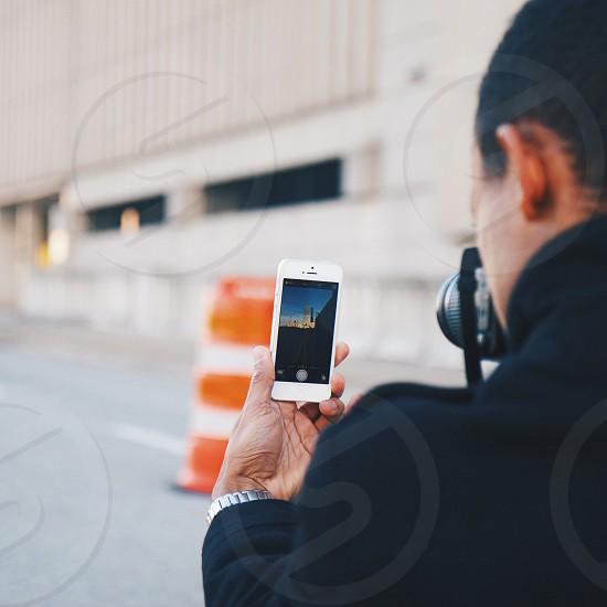 man holding dslr camera taking photo of white iphone 5 taking photo of orange white stripe drum photo