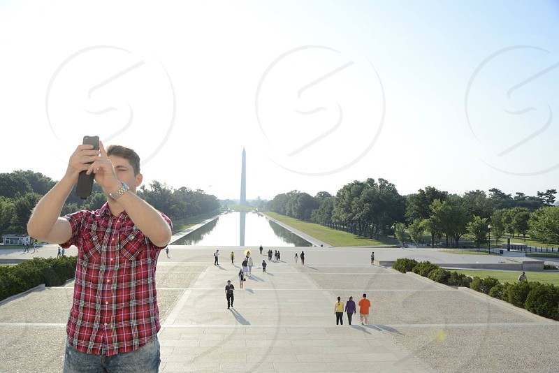 man standing holding mobile phone photo