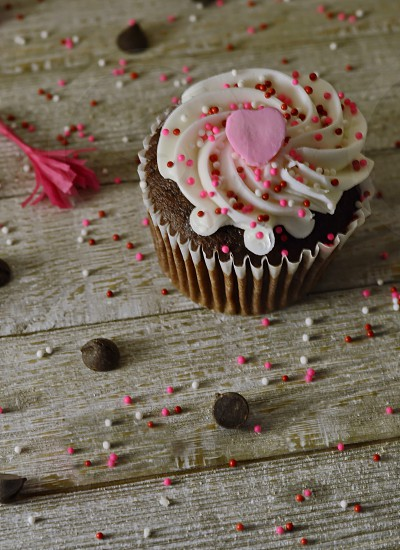 Fill in the heart with that special message. A single cupcake decorated for Valentine's day table has festive chocolate and sprinkles. photo