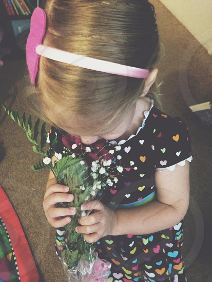 A little girl getting flowers from her daddy photo