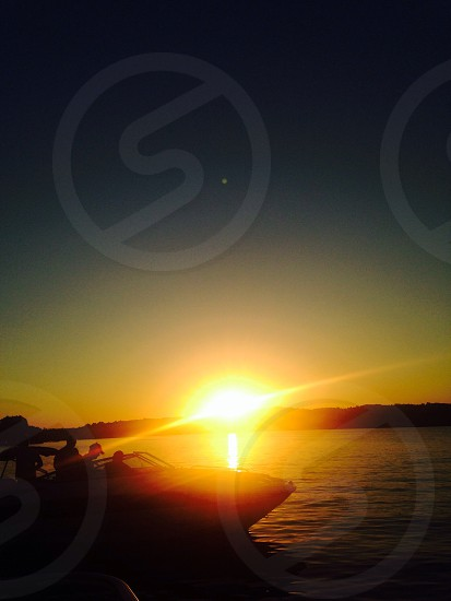 silhouette photo of 4-person riding on speedboat during sunset photo