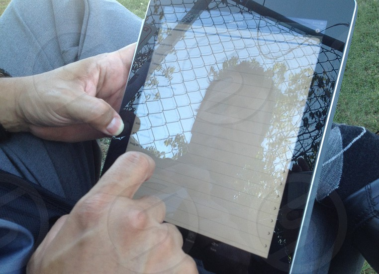 photo of man reflected in tablet photo