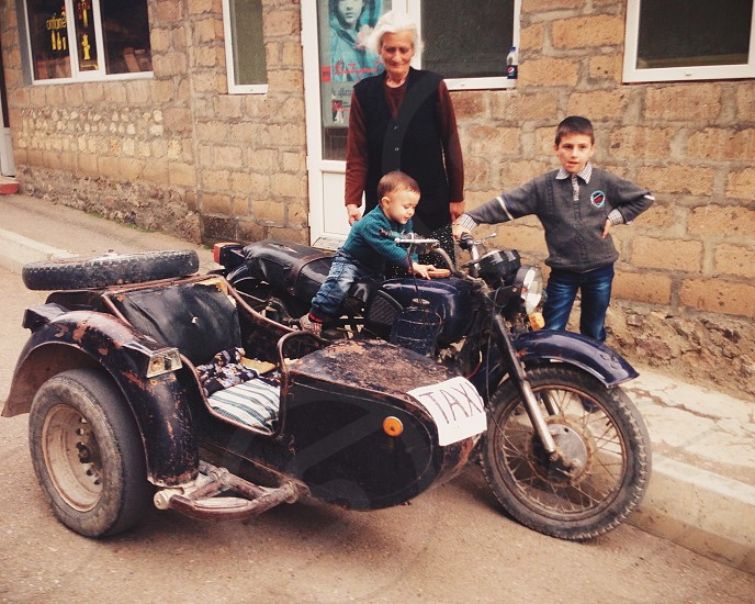 woman and two boy in tricycle photo