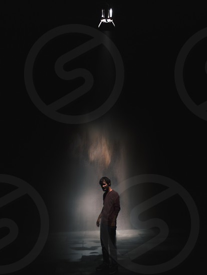 human standing in dark room with single light shining down photo