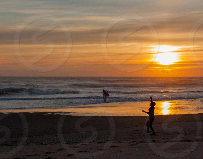 Boy Flying Kite on Beach in Sunset photo