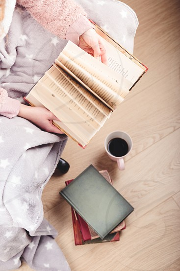 Girl enjoying the reading a book and drinking coffee at home. Young woman sitting on a chair wrapped in blanket holding book relaxing at home. Portrait orientation. View from above photo