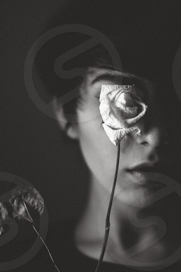 woman covering her right eye with white rose flower in grayscale photo