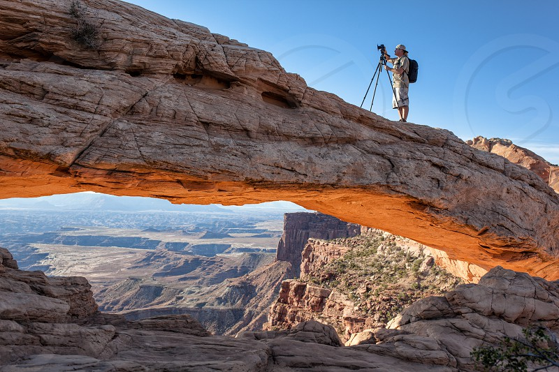 person setting a camera on a tripod while standing on brown rock photo