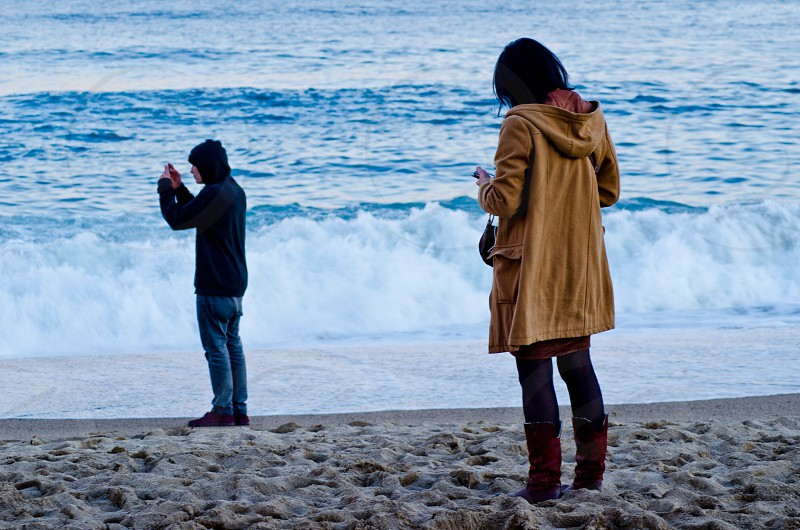 woman wearing brown trenchcoat and man wearing blue hoodie jacket on white beach photo