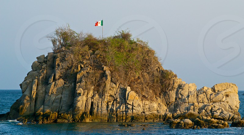 torn mexican flag in small rock island photo