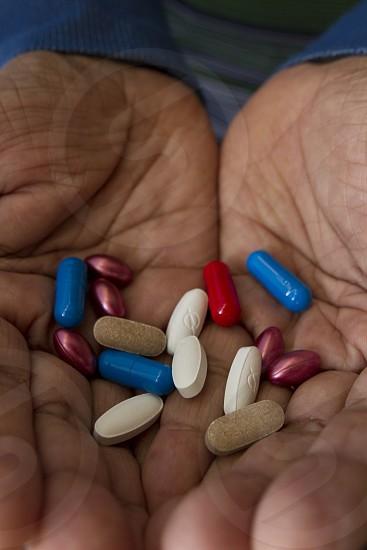 pile of pills in hands colorful diverse pills capsules medicines multi portrait closeup photo