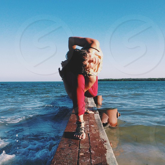woman on a brown wooden dock by the shore photo