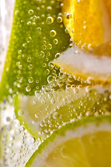 Homemade refreshing drink made from lemon and lime slices with bubbles. Macro photo of summer healthy lemonade photo