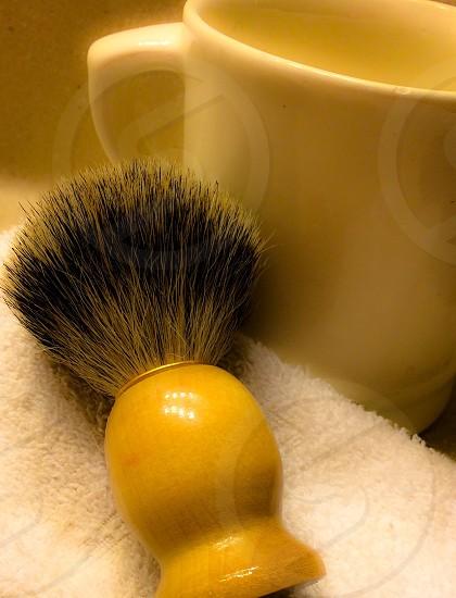 yellow handled black makeup brush beside white ceramic mug photo