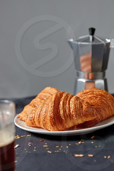 Italian coffee maker with morning hot aromatic beverage and homemade freshly baked french pastry on dark textile background. Place fo rtext. Continental breakfast. photo