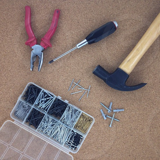 hammer screwdriver  pliers and a set of nails and screws on brown carpet photo
