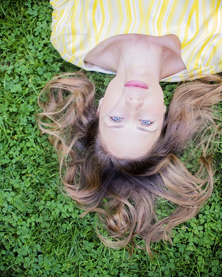 woman in yellow and white stripe scoop neck shirt lying on green grass during daytime photo