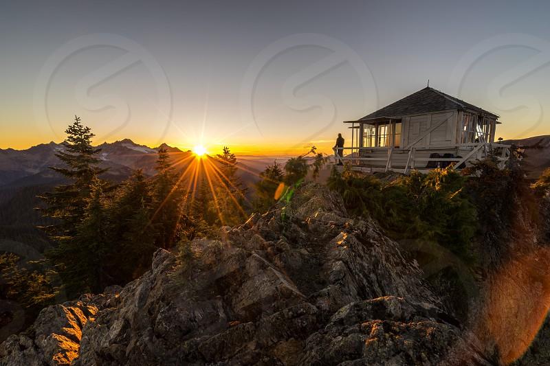 man standing on white wooden house veranda on mountain top under grey and orange sunset sky photo