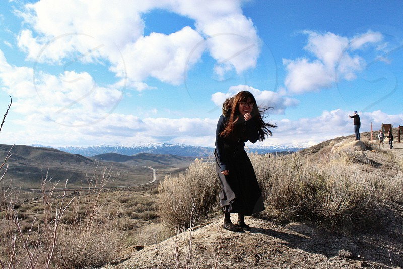 Woman wearing a black trenchcoat on the dirt hill photo