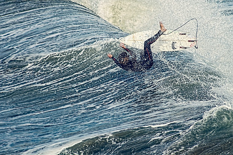 A surfer falls off his surfboard into a foamy wave photo