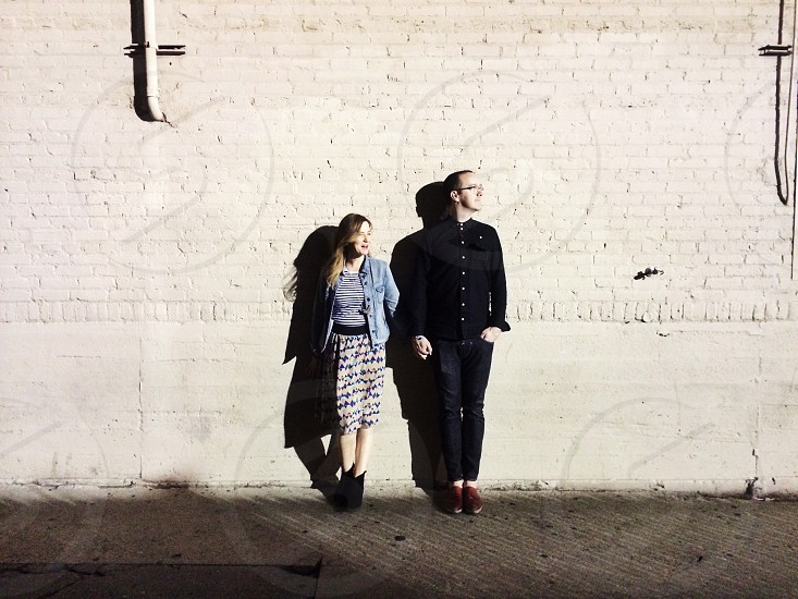 woman standing beside woman both leaning on the wall photo