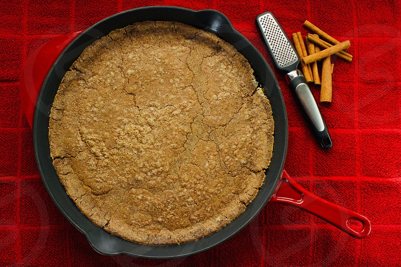 Overhead view of a freshly baked Cinnamon Sourdough Dutch Baby in a red cast iron skillet with cinnamon sticks and mini-grater on a red towel photo