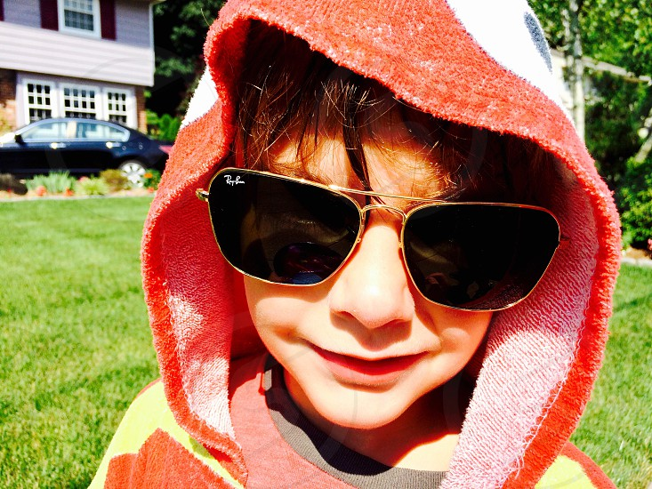 Boy wearing daddy's sunglasses and a towel hoodie. Kids.  photo