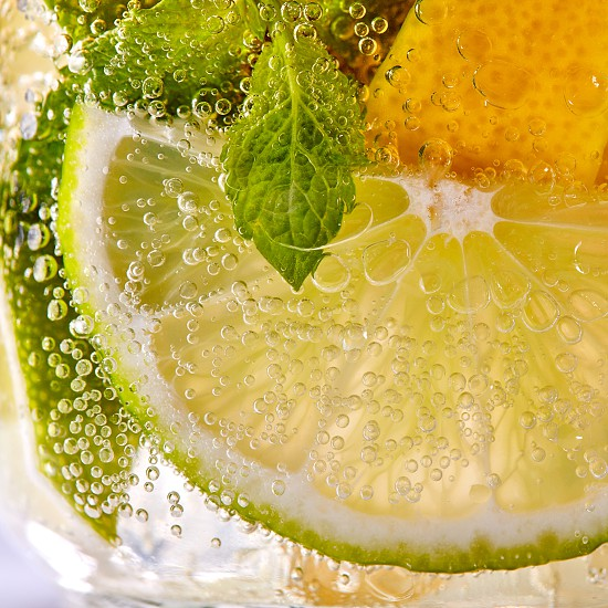 Green leaf of mint pieces of lemon and lime with bubbles in a transparent glass. Macro photo of summer cold mojito photo