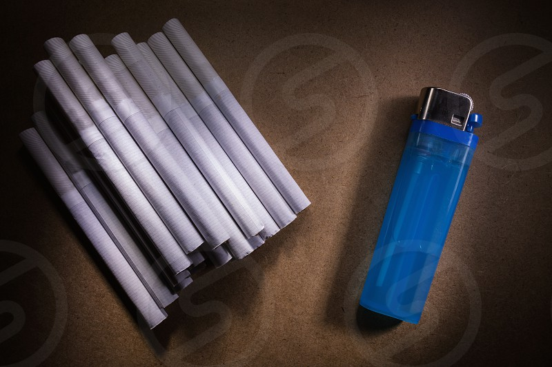 Abstract composition of cigarettes and lighter on brown surface.  photo