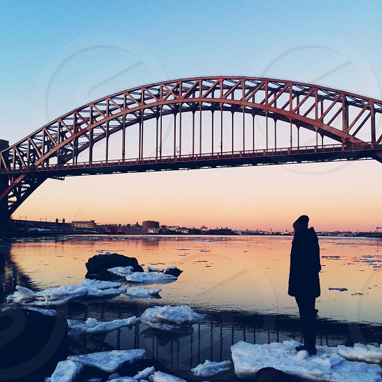 person wearing knit cap and coat on floating ice near red bridge photo