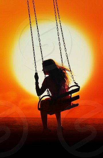 silhouette of woman on swing ride under orange sunset photo