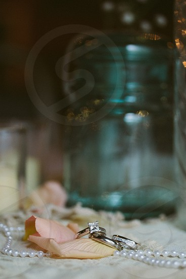 silver rings on a pearl necklace and pink petal photo