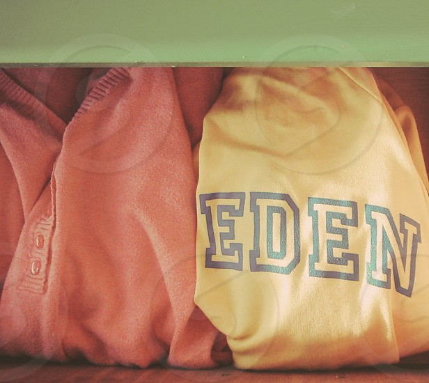 "A pink sweater next to a folded jogging suit folded into an ""Eden"" photo"