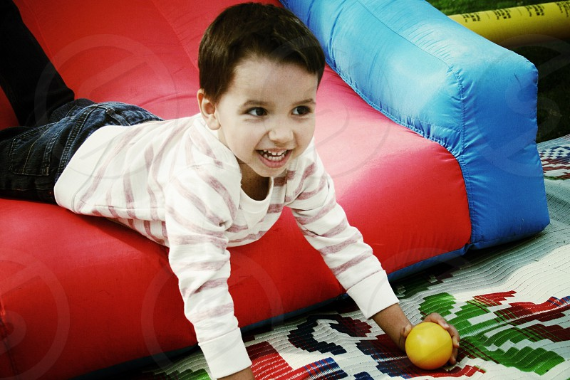 young boy on red and blue inflatable couch photo